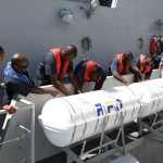 Marines going through a step by step procedure on how to deploy the life rafts during an emergency out at sea.