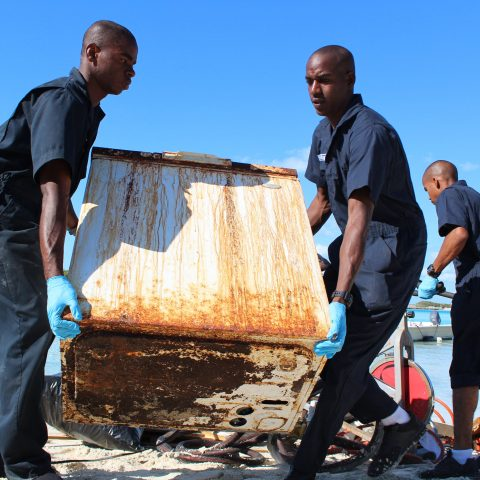 wo Defence Force Marine Recruits removing an old appliance at the Exuma Cays Land and Sea Park during a recent clean-up effort.