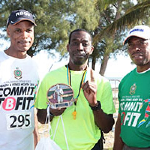 Mackey Williams receiving his award as the top male walker at the RBDF Fun Run/Walk and Health expo on April 14, 2018 also shown are: RBDF Commodore Tellis Bethel and Training Officer Lieutenant Origin Deleveaux Jr.