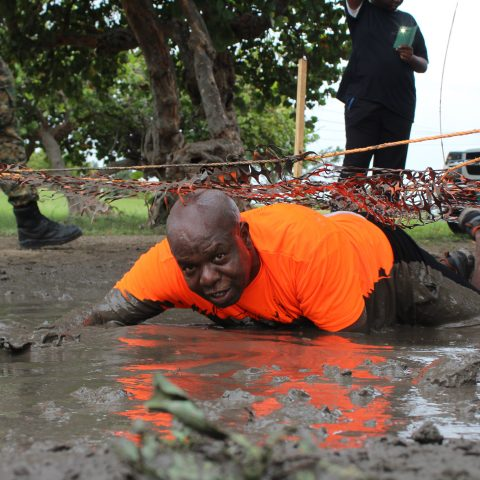 Petty Officer Perez Rolle getting down and dirty through the obstacle course at the Bahama Health Mud Run.
