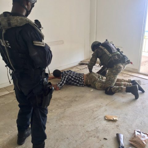 A Royal Bahamas Police Force Officer providing security as a Royal Bahamas Defence Focrce Marine searches an individual during a simulated exercise of the Tradewinds 2018 Exercise in St. Kitts.