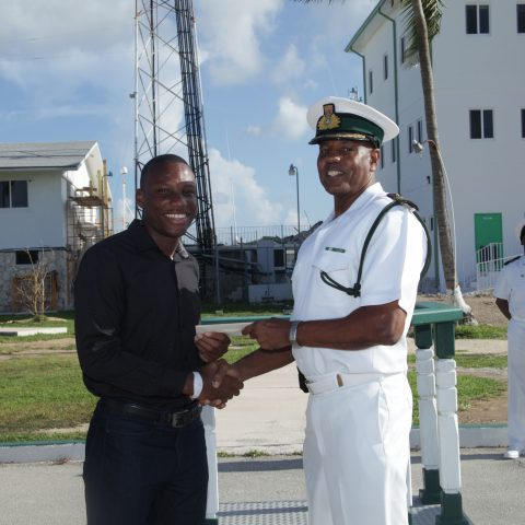 Yahshua Cox receiving a donation from Commander Michael Sweeting, Base Executive Officer on August 27 at HMBS Coral Harbour.