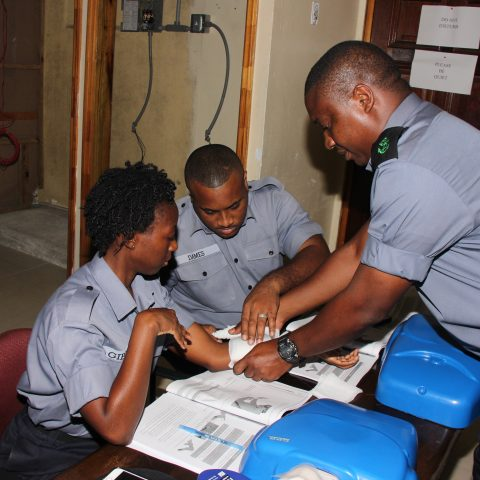 Marine Seaman Deon Dames and Woman Marine Myiesha Gibson controlling and stopping the bleeding by applying bandages in a simulation exercise during the American Heart Association First Aid and CPR Training at the Coral Harbour Base. Assisting with instructions is the Defence Force's Medical Center Instructor Leading Seaman Kevin Smith.
