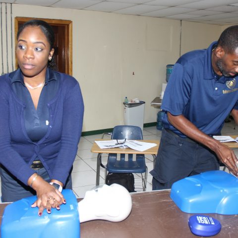 Representatives from The Bahamas Customs Department participating in a simulation exercise during the American Heart Association First Aid and CPR Training at the Coral Harbour Base. From left: Grade 2 Customs Officers Robyn Stuart and Lloyd Bodie.