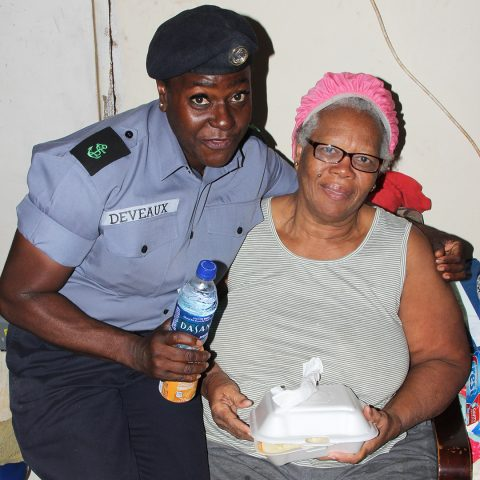 Gambier resident Miss Charlotte McPhee receiving a hot breakfast from Leading Woman Marine Monique Deveaux during the community outreach by members of the Defence Force's Supply Department on November 29, 2018.
