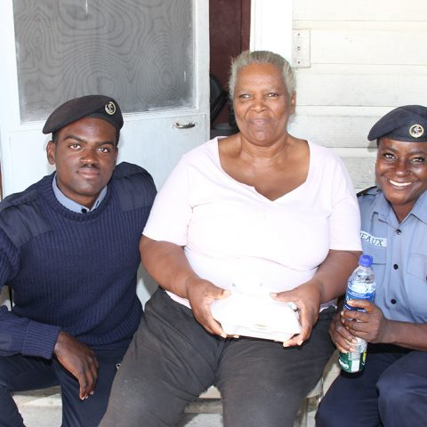 Leading Woman Marine Monique Deveaux and Marine Seaman Lendon Johnson delivering a hot meal to Miss Bernice Culmer during the community outreach by members of the Defence Force's Supply Department on November 29, 2018.
