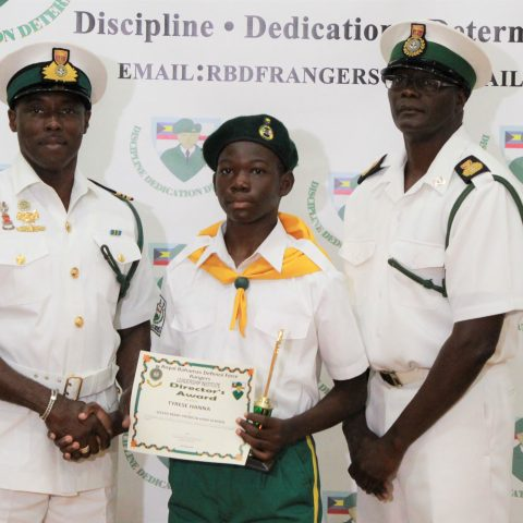 Tyrese Hanna of Sister Mary Patricia School, receiving the Rangers Director Award at the RBDF Rangers Passing out Parade ceremony in Grand Bahama on May 11, 2019. overall Minister of National Security Award. Also shown are: Lieutenant Commander Johnson, the commanding officer of the RBDF Freeport Base and Rangers Operations Senior Rate, Chief Petty Officer Pedro Bain.