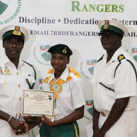 Bynaj Rolle of Mary Star Academy receiving the Commander Defence Force Academic Achievement Award at the RBDF Rangers Passing out Parade ceremony in Grand Bahama on May 11, 2019. Also shown are: Lieutenant Commander Johnson, the commanding officer of the RBDF Freeport Base and Rangers Operations Senior Rate, Chief Petty Officer Pedro Bain.
